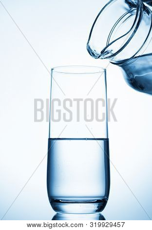 Pouring water from glass pitcher on blue background