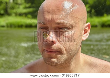 Bald man of mature age with a moth on the tip of his nose, against the background of a river in the wild, ecotourism. poster