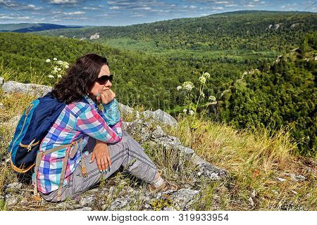 Beautiful woman in a plaid shirt and sunglasses is resting on the top of the mountain on a sunny summer day. She is engaged in hiking, and ecotourism, behind her a small backpack. poster