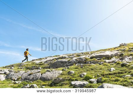 Latin American Man Hiking In The Mountain Wearing Backpack.. Latino Wearing Yellow Backpack Hiking I