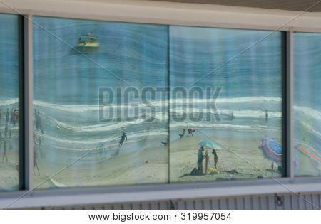 Beachgoers Reflections At Windows Of Lifeguard Tower At Newport Beach Park