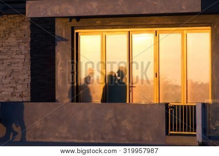Beachgoers Reflections At Windows Of A Beach House