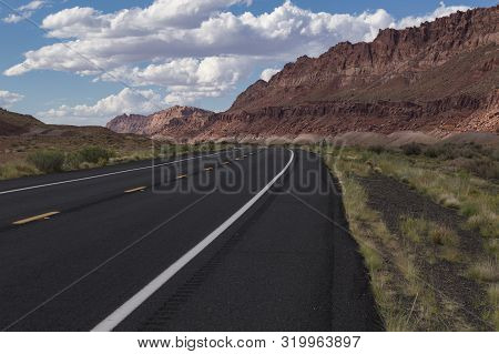 An Empty And Lonely, Two Lane Blacktop Road Leading Off Into A Range Of Rocky, Red Mountains In A Ba