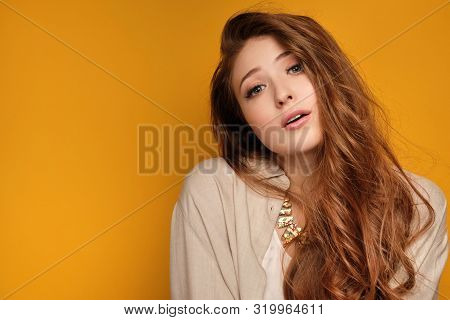 Red-haired Girl On An Orange Background Looking At The Camera With Her Head Bent To The Side And Her