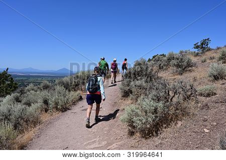 Hikers On Misery Ridge Trail In Smith Rock State Park Near Terrebonne, Oregon On A Cloudless Summer