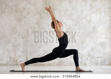 Young Woman Practicing Yoga, Standing In Warrior One Pose, Virabhadrasana