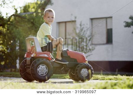 The Little Boy Is Playing Driving Tractor Toy At The Street Outdoors.