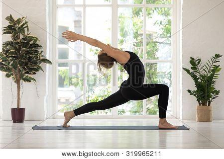 Beautiful Woman Standing In Warrior One Pose, Yoga Virabhadrasana Exercise