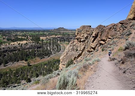 Woman hikes and photographs Misery Ridge Trail in Smith Rock State Park near Terrebonne, Oregon on cloudless summer day. poster