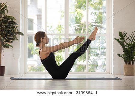 Young Woman Doing Paripurna Navasana Exercise, Boat, Practicing Yoga