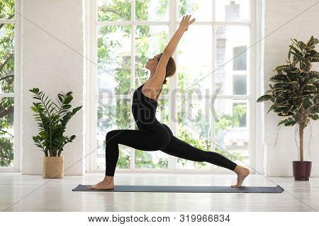 Young Woman Standing In Warrior One Pose, Yoga Virabhadrasana Exercise