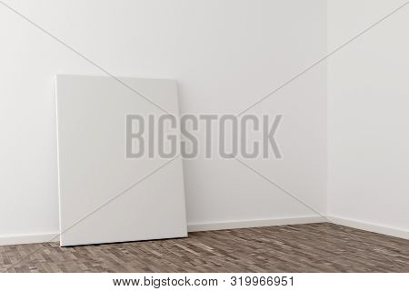 Empty Picture Frame Canvas Leaning Against White Wall In Bright Room With Brown Wooden Floor With Co