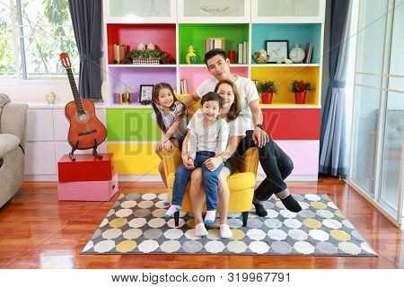 Full Shot Happy Asian Family Father, Mother, Child Daughter And Son Sitting On Sofa In Colorful Mode