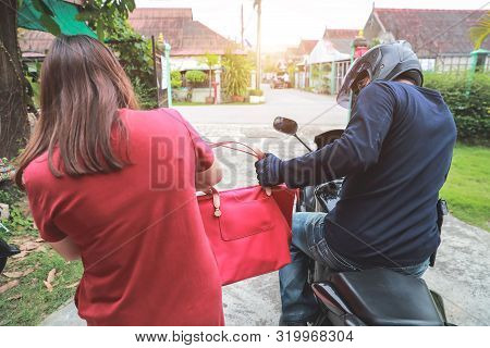 Thief On Motorcycle With Gun Trying To Steal Bag Or Money From Unaware Woman On Street (theft Concep