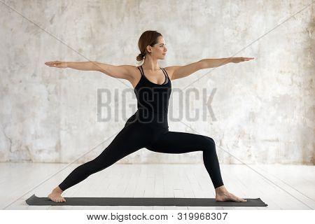 Young Woman Practicing Yoga, Standing In Warrior Two, Virabhadrasana