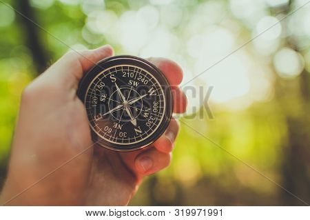 Compass In A Hand Of Hiker. Useful Equipment On A Trailhead.