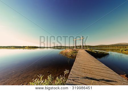 A Wooden Path Leads To A Swing By A Lake In The Finnish Lapland. The Swing Is Built On An Island In