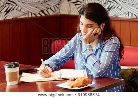 Young Bored Woman Sitting At Cafe Table, Listening To Lection In Earbuds And Writing Down Important