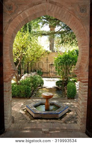Ronda, Spain - May 13, 2008 - View Through A Moorish Archway Towards The Fountain And Garden In The