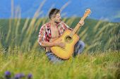 Playing music. Sound of freedom. Inspired musician play rock ballad. Compose melody. Inspiring environment. Man with guitar on top of mountain. Acoustic music. Summer music festival outdoors poster