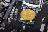 bitcoin physical shiner in cpu socket of modern cpu motherboard with selective focu and blur poster