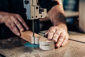 Carpenter working in workshop. Joiner labourer cuts wooden plank on jigsaw machine. Handwork, carpentry concept, woodworking. poster
