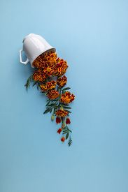 Coffee Or Tea Cup With Marigold Flowers On A Blue Background