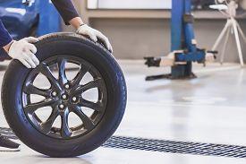 Asian Man Mechanic Inspection Service Maintenance Car Holding Tyre Or Tire Car Inspection For Measur