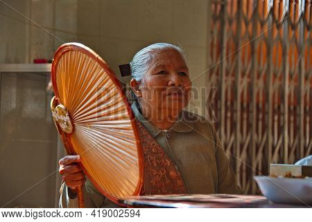 Mandalay. Myanmar. November 22, 2016. An Elderly Emotional Woman Is Happy To Receive Guests Of A Bud