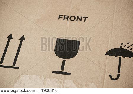 Word Front And Three Symbols On Cardboard Box - This Way Up, Keep Dry And Fragile For Careful Transp