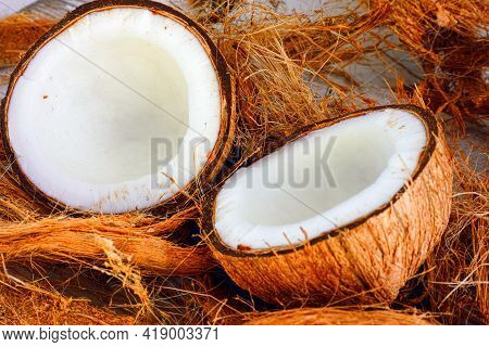 Two Halves Of Coconut On Coconut Fiber Background. Close-up