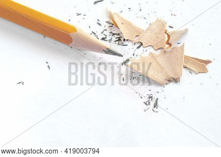 The Pencil After Sharpening Lies On A White Background Next To The Scales