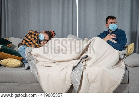 Young Couple Lies On The Bed At A Distance Covered With A Blanket With Protective Medical Masks On T
