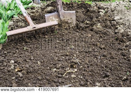 A Dug Up Bed Of Earth A Shovel Is Stuck In The Ground In The Foreground A Rake In A Blur