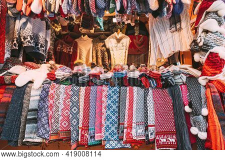 Traditional Christmas Winter Market Trading Houses With Warm Clothes, Wear And Hats. Colorful Knitte