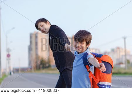 Brothers Go To School. The Teenager And His Younger Brother With Backpacks Hold Hands, Brothers Smil