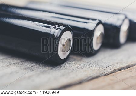 Black Rechargeable Lr6 Aa 1.5v Batteries On A Wooden Table