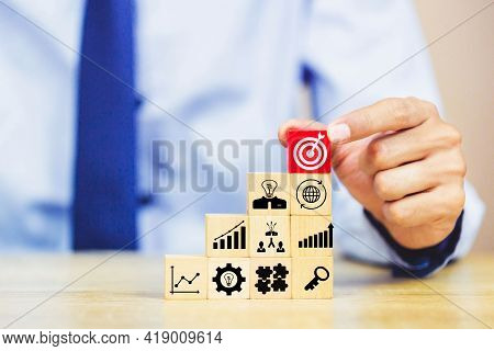 Businessman holds a target with an arrow and gradually stacks wooden blocks