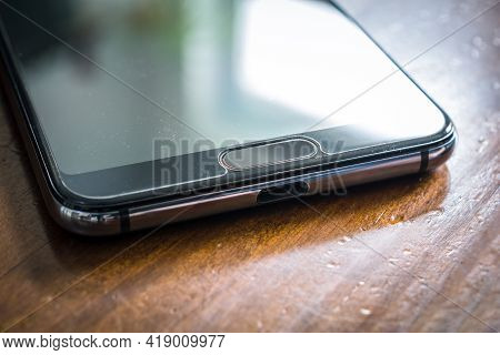 Black Smartphone With Window Reflection Lying On A Brown Wooden Table