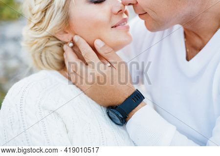 Man In A White Sweater And Black Watch Kisses A Woman In A White Sweater And Beautiful Earrings