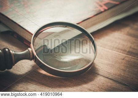 Vintage Magnifying Glass Leaning On The Corner Of An Old Book
