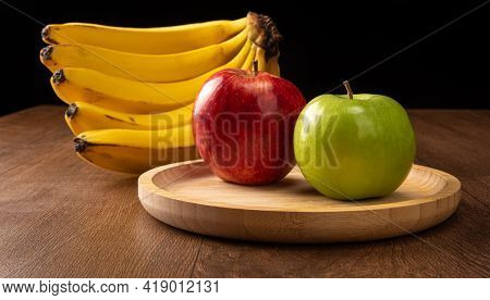 Green And Red Apples Positioned On Black Plate And Bananas On Wood, Black Background, Selective Focu