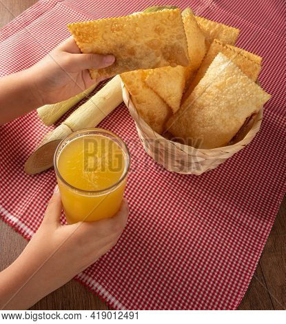 Hands Picking Up Brazilian Fried Pasteis And A Glass Of Cane Juice, And Canes Positioned On A Checke