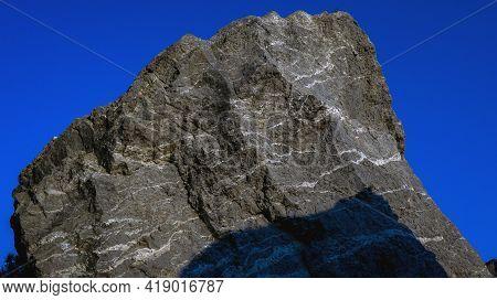 Gray Granite Rock Against The Blue Sky.