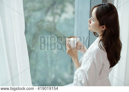 Pensive Young Woman Drinking Cup Of Morning Coffee And Looking Outside Through Apartment Window
