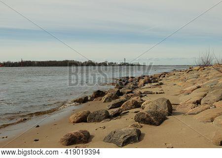 Rocky Coast At Mangalsala, Riga, Latvia, Europe From Distance Viewable Black-white Lighthouse. Stony