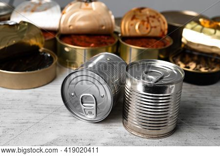 Many Cans With Conserved Fish On Wooden Table