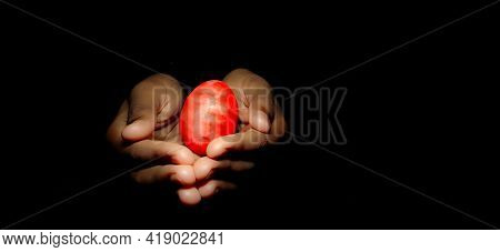 Closeup Of Hand Holding Colourful Easter Egg In A Isolated Black Background With Selective Focus On