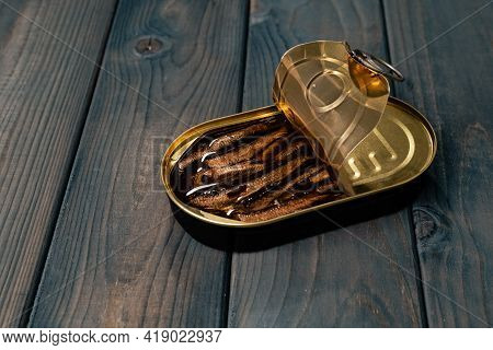 Canned Fish In Sauce Conserve On Dark Wooden Table
