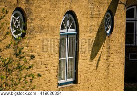 Close Up Of An Old Historical Yellow House With Old Windows